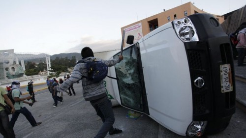 Student teacher smashes a car during a protest in support of the missing students of Ayotzinapa Teacher Training College Raul Isidro Burgos outside the government palace of Guerrero state in Chilpacingo